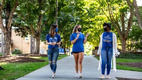Three female college students wearing mask walking outdoors on campus